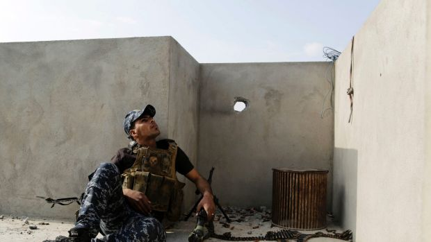 An Iraqi federal police soldier seeks cover on a roof of a house in Mosul.
