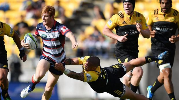 Nic Stirzaker is tackled by the Hurricanes' TJ Perenara.