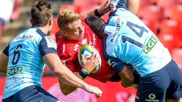 Ruan Ackermann of the Lions is upended by Waratahs Jack Dempsey and Reece Robinson in Johannesburg on Saturday.