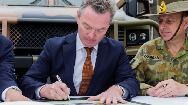 Minister for Defence Industry Christopher Pyne signs the acceptance of the last two Hawkei Pilot vehicles at a ceremony ...