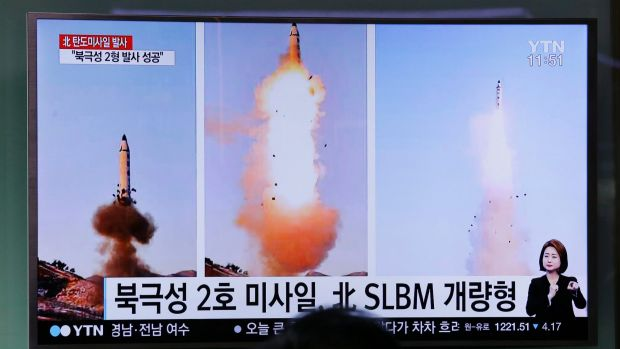 A man in South Korea watches a news program showing photos published in North Korea's Rodong Sinmun newspaper of North ...
