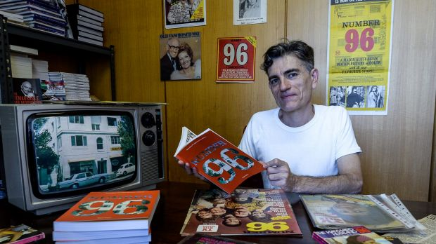 Super-fan: Melbourne historian Nigel Giles with his new book about  <i>Number 96</i>, and some of the memorabilia he has ...