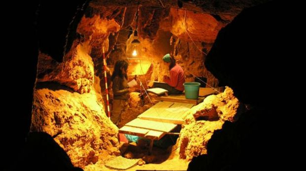 Scientists work in a cave, where 12 Neanderthal specimens were found.
