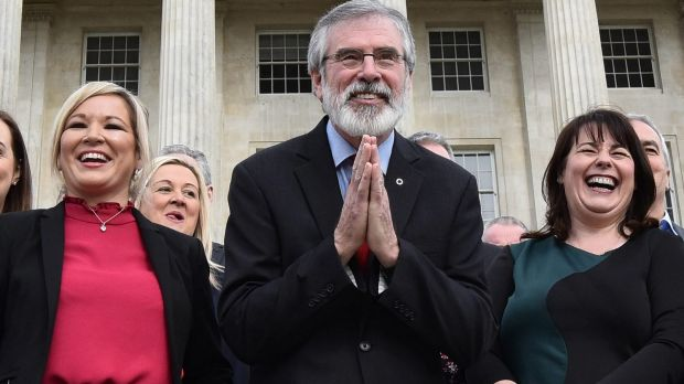 Sinn Fein president Gerry Adams, centre, bows to a group of Japanese tourists as he attends a press call alongside ...