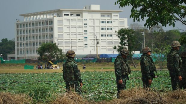 Troops stand in front of an unfinished medical centre at the Wat Dhammakaya temple compound in Pathum Thani province, ...