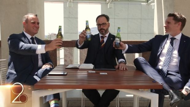 Liberal MPs Tim Wilson, left, and Andrew Hastie, right, hold up Coopers beer bottles in the video.