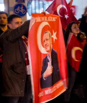 A demonstrator holds a poster of Turkish President Recep Tayyip Erdogan  outside the Turkish consulate in Rotterdam.