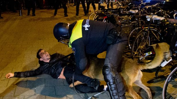 A Dutch riot policeman tries to get his dog to let go of a man after riots broke out at the Turkish consulate in Rotterdam.