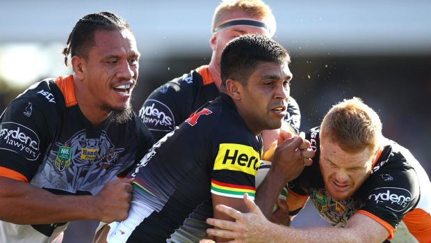 Through the middle: Tyrone Peachey is wrapped up by three Tigers defenders.