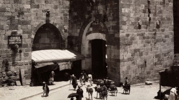 """An 1894 photograph from Maison Bonfils of Jerusalem's Jaffa Gate. A sign on the left directs visitors to """"Cook's Tourist ..."""