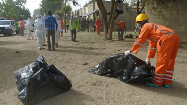 Emergency personnel collect bodies following an attack by suicide bombers at the outskirts of Maiduguri, Nigeria last month.