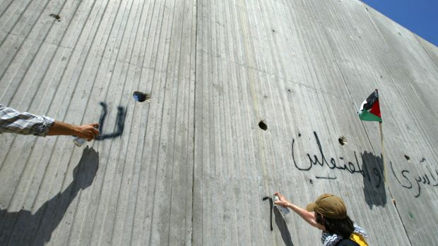Foreign activists spray graffiti on the wall erected by Israel near the northern West Bank town of Qalqilya, which is ...