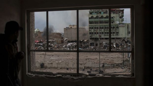 Window to destruction: an Iraqi Federal Police soldier takes cover inside a destroyed building during fighting against ...