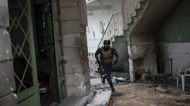 An Iraqi Federal Police soldier runs for cover during fighting against Islamic State miltants in western Mosul on Thursday.