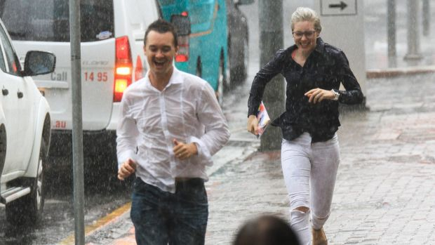 Pedestrians run for shelter from the rain in the CBD.