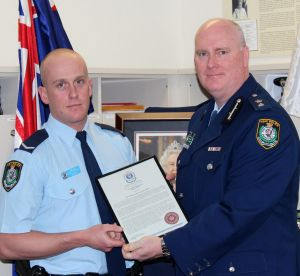 Chris Sheehy (left) receives a bravery award from Newtown Police Commander Simon Hardman in September 2015. The young ...