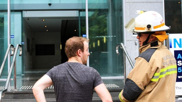 Ben Harrison speaks to a firefighter after a fire alarm and building evacuation on Turbot Street, Brisbane.