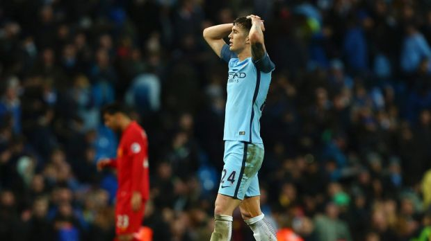 Opportunity spurned: Manchester City's John Stones leaves the field after taking just a point against Liverpool at home.