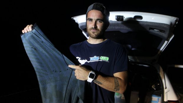 Gonzalo Mompo Fernandez shows the teeth marks on his wetsuit after he was bitten by a shark.