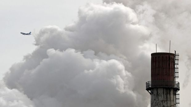 An airliner flies past a coal-fired power plant in Beijing last month.