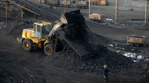 A worker watches a bulldozer unload coal at a mine in central China's Anhui province.