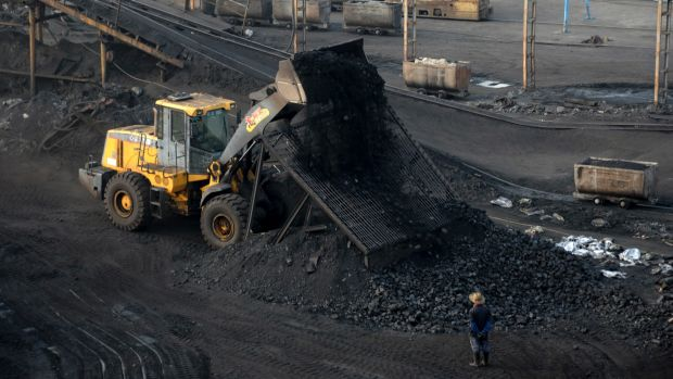 A worker watches a bulldozer unload coal at a mine in central China's Anhui province last month.