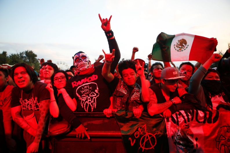 Fans bathed in red light cheer on Mexican metal band Brujeria during Vive Latino in Mexico City.