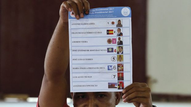An election worker holds up a ballot during the presidential election's vote counting at a polling station in Dili, East ...