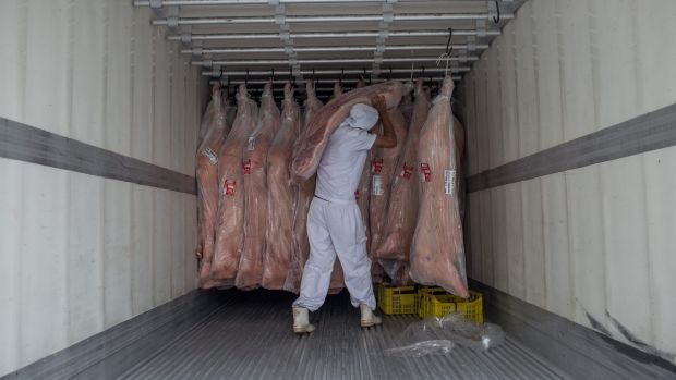 A butcher hangs meat in a container in Sao Paulo, Brazil.