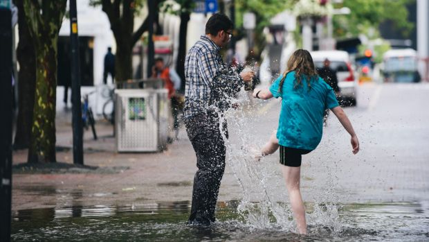 Friends Jayden Goodrem, 18, of Paige, and Ashleigh Peet, 19, of Kambah enjoy a puddle in Garema Place.