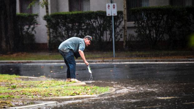 A man retrieves a thong after losing it on a waterlogged Kingston street on Tuesday.