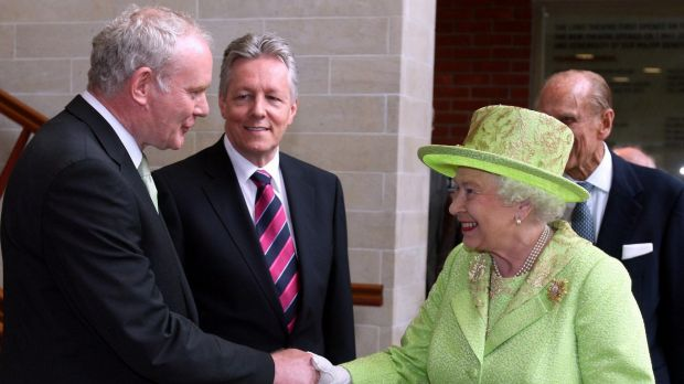 The Queen shakes hands with Martin McGuinness, watched by then first minister Peter Robinson, centre, at the Lyric ...