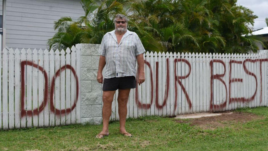 Graham Wilson with the defiant message on his fence for Cyclone Debbie.