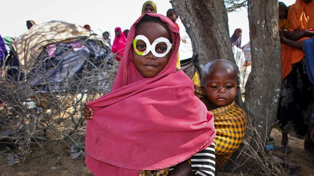 A young Somali girl displaced by drought wears mock spectacles cut from an antibiotics medicine box at a relief camp ...