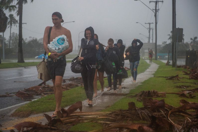 Travellers from England, Germany and Finland leave the Bowen cyclone evacuation centre after this mornings all clear.