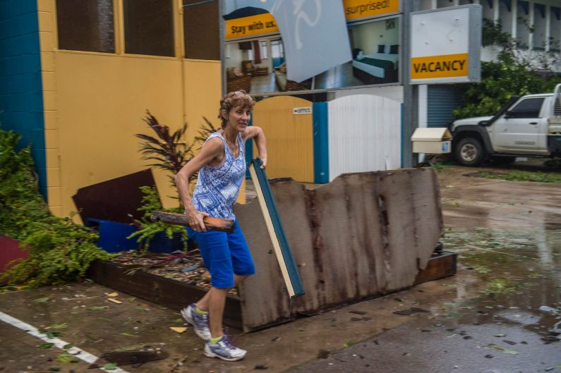 A local cleans up the debris at the Sky View Units on the foreshore of Bowen.