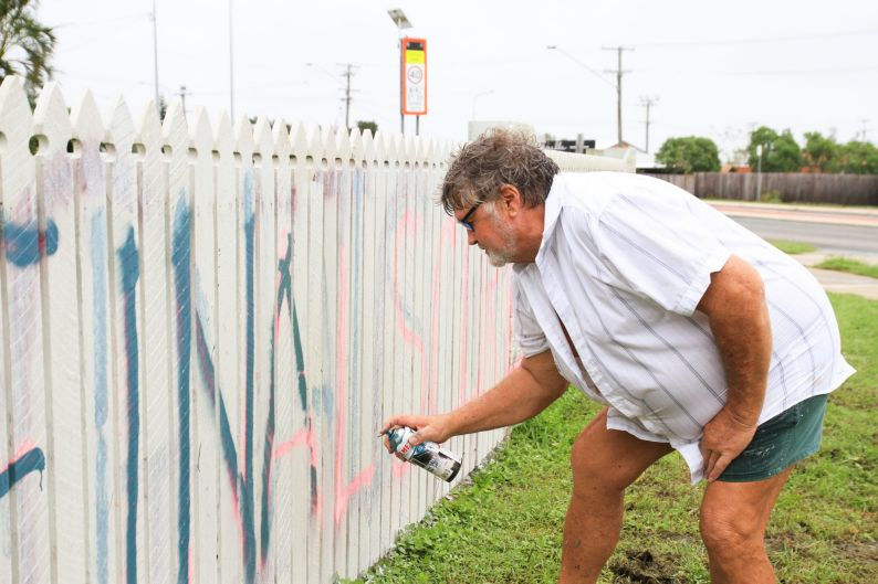 Graham Wilson of Bowen paints a fresh message on his fence in the wake of Cyclone Debbie.