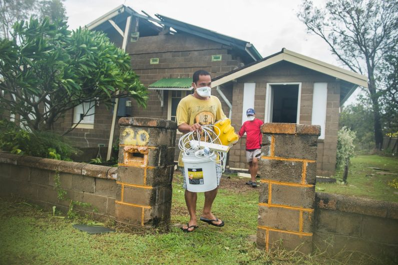 Joel Medil empties his Cyclone Debbie damaged house in Bowen, wearing a mask to protect from the asbestos.