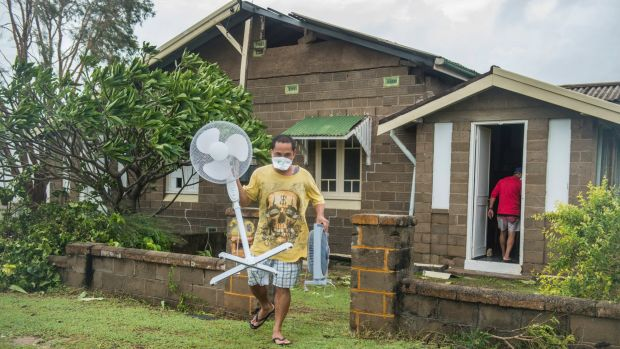 Bowen resident Joel Medil empties his cyclone-damaged home.