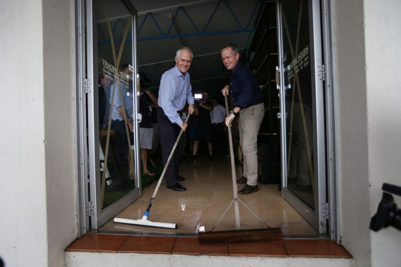 Australian PM Malcolm Turnbull Opposition Leader Bill Shorten sweep water from a store in a cyclone damaged area March ...