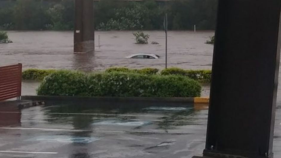 The top of a vehicle can be seen in floodwaters at Toombul.