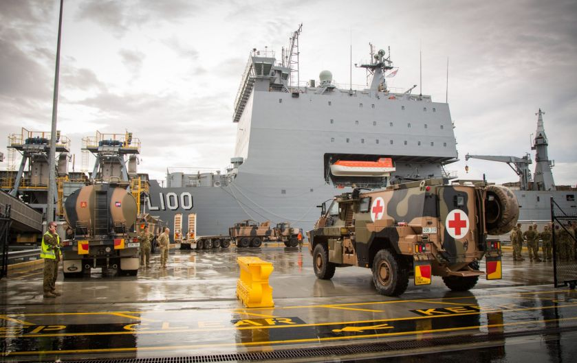An Australian Army Bushmaster Protected Mobility Vehicle (ambulance variant) waits to be loaded.