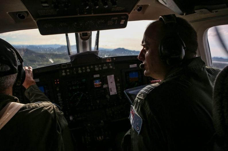 Commanding Officer of No 38 Squadron, Wing Commander Michael Ward flies a RAAF KA350 King Air over areas damaged by ...