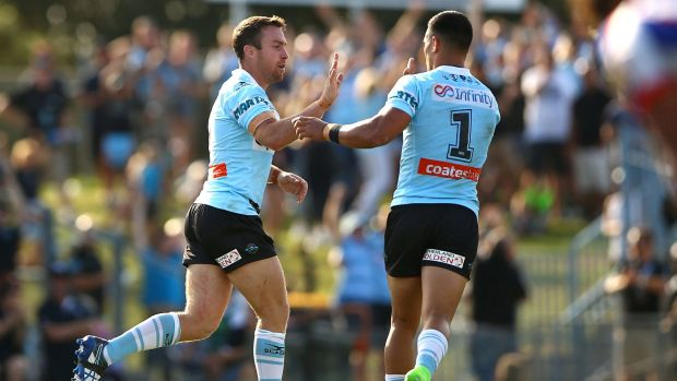 James Maloney (left) of the Sharks celebrates kicking a field goal.