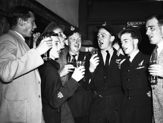 A group celebrate after the Sydney march in 1946 with a song and a beer.