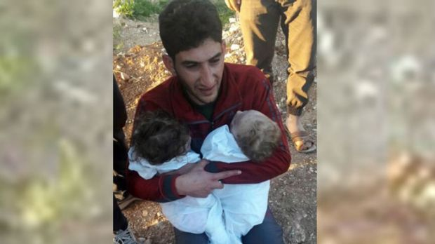 A man holds his twin toddlers who were killed during the chemical weapons attack in Syria.