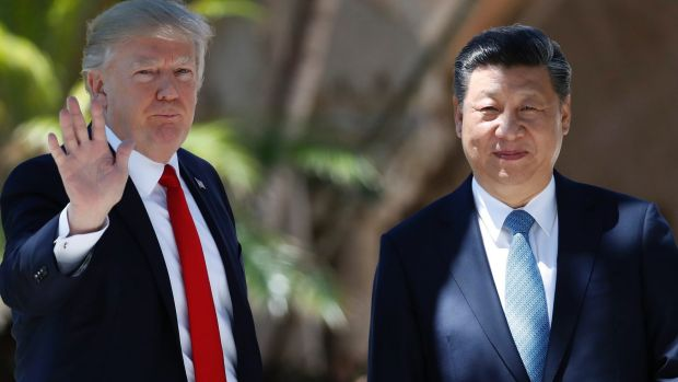President Donald Trump and Chinese President Xi Jinping pause for photographs at Mar-a-Lago, on Friday.