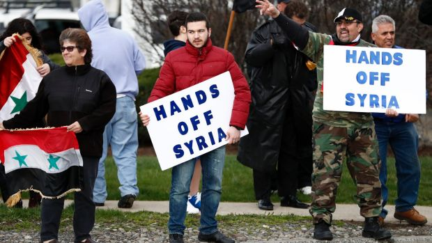 People hold signs during a rally in opposition to the US airstrikes in Syria in Allentown, Pennsylvania. Allentown has ...