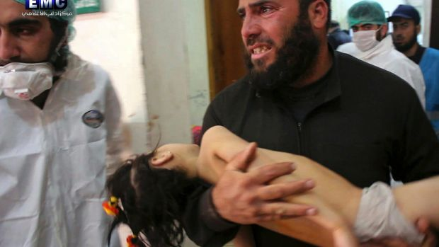 This picture, provided by the rebel-controlled Idlib Media Centre,  shows a man carrying a child into hospital following ...