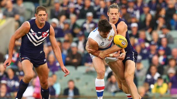 Nat Fyfe tackles Tom Campbell during the round three AFL match between the Fremantle Dockers and the Western Bulldogs at ...